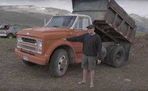 Roadkill Extra host David Freiburger stands nexts to a 1969 Chevy C50 dump truck.