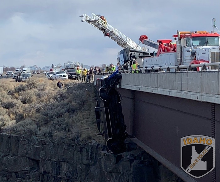 A Ford F-350 hangs by a trailer safety chain from an I-85 bridge over Malad Gorge in Idaho as rescuers scramble to save the couple and their dogs inside.