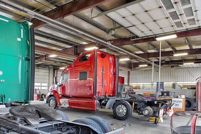 Semi-trucks receiving maintenance work in a garage