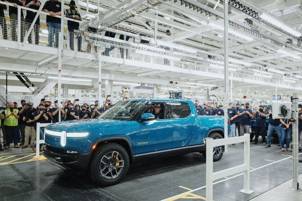 Rivian CEO RJ Scaringe is shown behind the wheel of his company's first factory-produced all-electric pickup, the R1T.