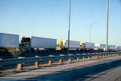 line of semi trucks in traffic